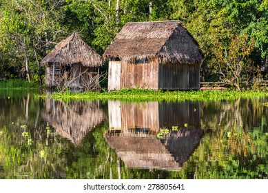 Two shacks reflected in the Amazon rainforest near Iquitos, Peru