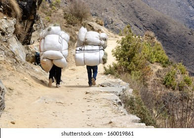 Two sherpa porters carrying heavy sacks in the Himalayas at Everest Base Camp trek ,Nepal.Sherpas are elite mountaineers and experts in the Himalaya mountains.