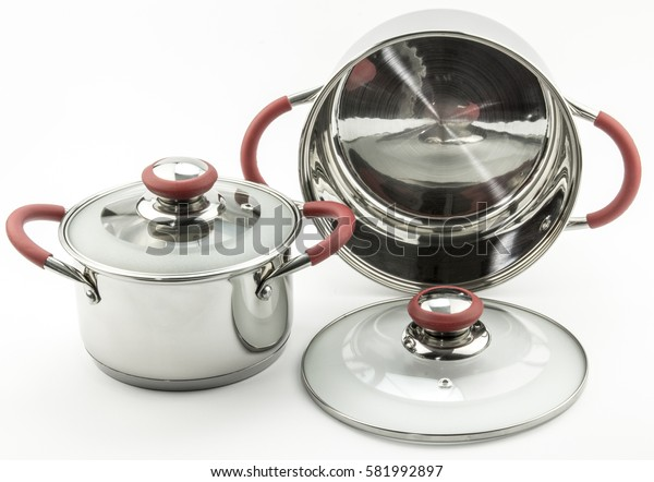 Two shiny new kitchen pots with glass lids and red handles