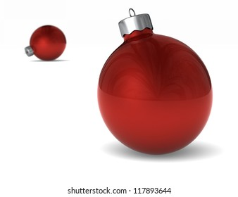 Two shiny red Christmas ornaments with one in the background out of focus