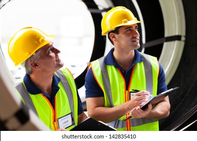 two shipping company employees inspecting tires after importing