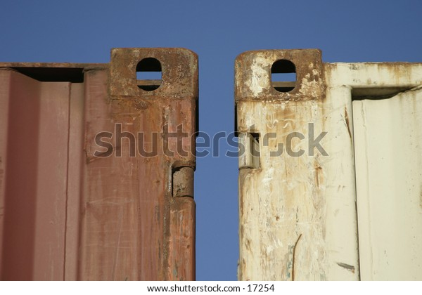 Two shipping containers against a blue sky