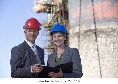 Two shipping engineers in front of an oil platform in the harbor