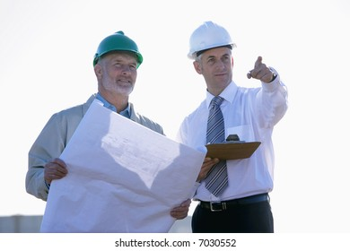 Two shipping engineers studying plans and pointing