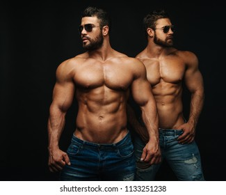 Two shirtless hunks at black background