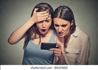 Two shocked women displeased young girls looking at mobile phone seeing bad news message or photos with disgusting emotion on face isolated on gray wall background. Human emotion, reaction, expression
