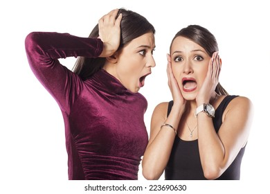 Two shocked young woman on white background