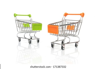 Two shopping carts on white background with reflections