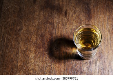 Two shot glasses of Brazilian gold and white cachaca isolated on rustic wooden background