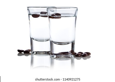 Two shot glasses with Italian Sambuca hard liquor surrounded by coffee beans isolated on white background