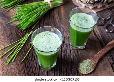 Two shots of barley grass juice with fresh and powdered plant
