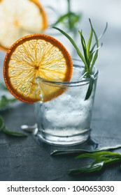 Two shots of cocktails with ice, dried orange slice and fresh tarragon on a grey table.