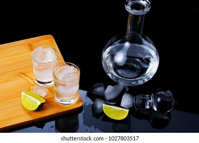 Two shots with strong alcohol on a wooden Board with ice cubes inside. Next is the glass carafe, lay the lime slices. Near the carafe are ice cubes and the lid from the carafe.