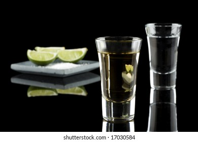Two shots of tequila with fresh lime slices and salt on a stylish plate isolated on a black background