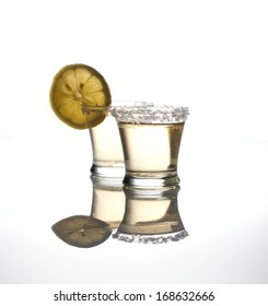 Two shots of tequila on white background with reflections