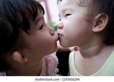 Two sibling kiss each other with love.