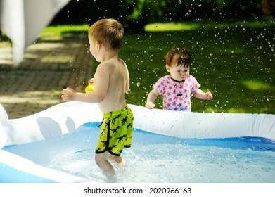 Deux enfants en bas âge et une petite fille jouant dans la petite piscine d'eau à l'arrière-cour