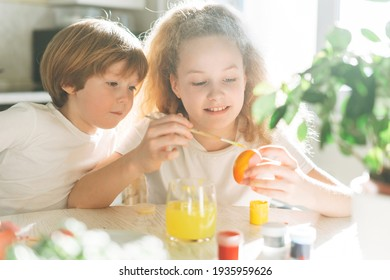 Two siblings brother and sister toddler boy tween girl painting easter eggs on kitchen at home on spring sunny day