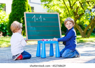 Two siblings children at blackboard practicing math, outdoor school or nursery. Happy kid boys counting and having fun together.