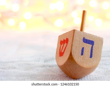 "Two sides of a dreidel Jewish toy that is played with at Hanukkah, the festival of lights.  Translations:  Hebrew alphabet, the red letter means shin or ""there"", the blue letter hey for ""happened""."