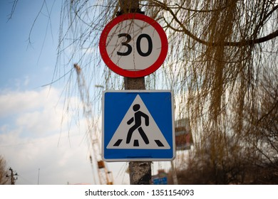 Two signs - speed limit 30 and pedestrians cross.