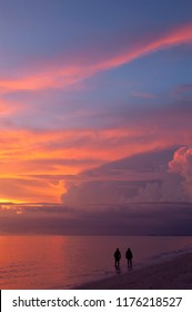 Two silhouetted people are wading along Barefoot Beach in the yellow, pink, orange and blue colors of sunset.