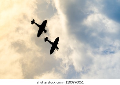 Two silhouetted spitfires dive out of the bright sun, as if attacking an enemy with surprise. Hiding in the sun is an effective and common air fighter tactic to catch their foe off guard