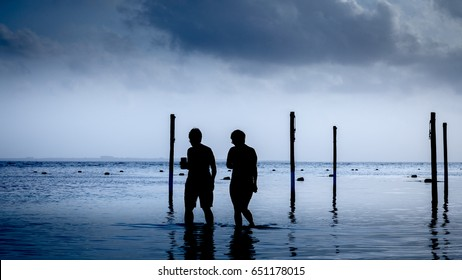 Two silhouettes figures walking on the beach