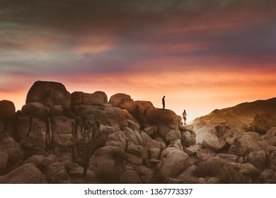 Two Silhouettes of Men Walking Along Boulders in High Desert - Sunset in Joshua Tree National Park