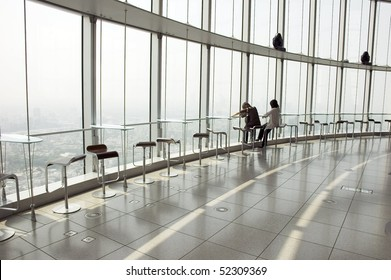 two silhouettes on the big window with panoramic view of Tokyo, Japan