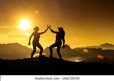 Two Silhouettes of the same woman giving herself high five on a mountain peak at sunrise, composed together in image editing