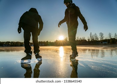 Two silhouettes: teenage boys are ice skating on the crystal clear frozen lake in Northern Sweden - ice like big mirror. One stands with his back to camera and going to skate, another waits his turn