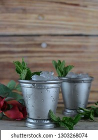 two silver mint julep cups with crushed ice and fresh mint in a rustic setting with red roses. Vertical image with copy space