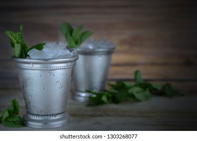 two silver mint julep cups with crushed ice and fresh mint in a rustic setting. Vignette added. Copy space