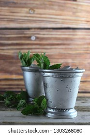 two silver mint julep cups with crushed ice and fresh mint in a rustic setting, vertical, copy space