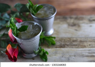 two silver mint julep cups with crushed ice and fresh mint in a rustic setting with red roses and copy space