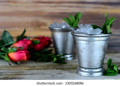 two silver mint julep cups with crushed ice and fresh mint in a rustic setting with red roses