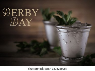 two silver mint julep cups with crushed ice and fresh mint in a rustic setting