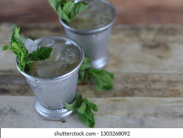 two silver mint julep cups with crushed ice and fresh mint in a rustic setting. Copy space