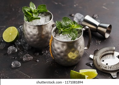 Two silver mugs of moscow mule or mint julep cocktail with crused ice, mint and lime on dark concrete background