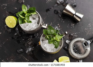 Two silver mugs of moscow mule or mint julep cocktail with crused ice, mint and lime on dark concrete background. Top view