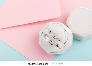 Two silver wedding rings with diamonds in white velvet jewelry box. White gold rings with gems on pink envelope background