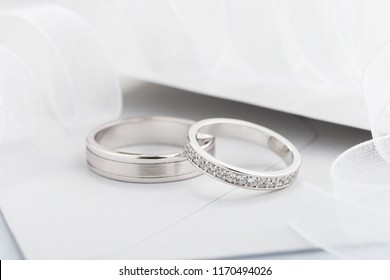 Two silver wedding rings with diamonds on gray background. White gold rings with gems. Wedding invitation concept with envelope