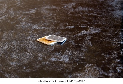 Two SIM cards on a black marble table.