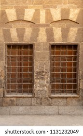 Two similar adjacent wooden closed windows with iron grid over decorated stone bricks wall, Medieval Cairo, Egypt
