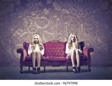Two similar women sitting on a sofa