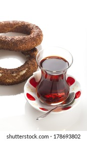 two simit that is circular bread on white dish with tea