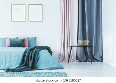 Two simple posters in gold frames hanging on the wall above double bed standing in bright interior with drapes