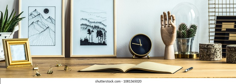 Two simple posters placed on a wooden desk with notebook, black and gold clock and cactus