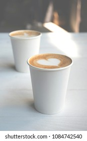 Two simple white paper cups of coffee take-away on white wooden table.